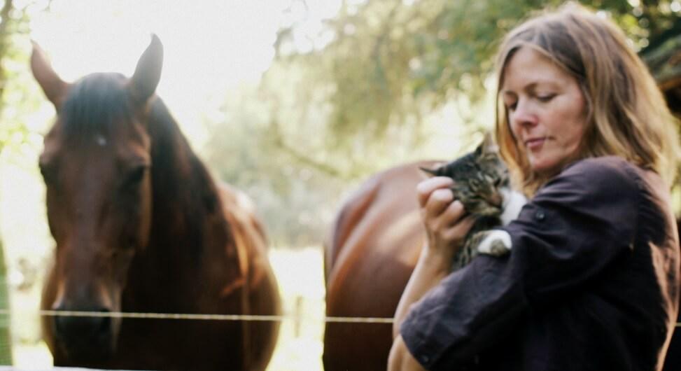 Zdjęcie Kingi Bec z kotem na rękach i końmi w tle.